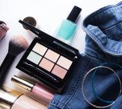 Взгляд сверху рубашки джинсов женщины, паллета concealer, лоска губы, маникюра, браслета, щетки порошка на белой предпосылке Стоковые Фото