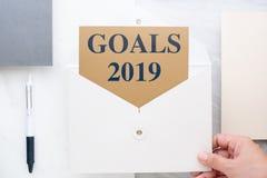 Взгляд сверху руки держа белизну охватывает с целями ` 2019 Новых Годов Стоковое фото RF