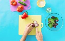 Взгляд сверху, руки плоского положения мужские варя салат Стоковые Изображения