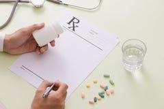 Взгляд сверху руки ` s доктора писать рецепт Bottl пилюльки Стоковая Фотография RF