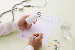 Взгляд сверху руки ` s доктора писать рецепт Bottl пилюльки Стоковое Изображение RF
