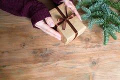 Взгляд сверху рук женщины с простой елью подарочной коробки и рождества на деревянной предпосылке стоковые фотографии rf