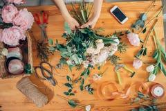 Взгляд сверху рук флориста молодой женщины создавая букет цветков Стоковые Изображения RF