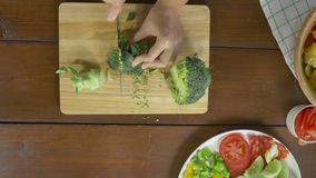Взгляд сверху салата женщины главного делая здоровые еда и брокколи прерывать на разделочной доске в кухне акции видеоматериалы