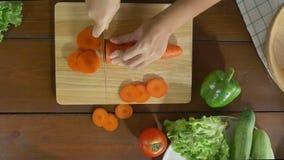 Взгляд сверху салата женщины главного делая здоровые еда и морковь прерывать на разделочной доске в кухне сток-видео