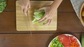 Взгляд сверху салата женщины главного делая здоровые еда и салат прерывать на разделочной доске в кухне сток-видео