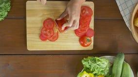 Взгляд сверху салата женщины главного делая здоровые еда и томат прерывать на разделочной доске в кухне акции видеоматериалы