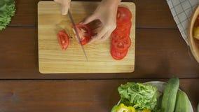 Взгляд сверху салата женщины главного делая здоровые еда и томат прерывать на разделочной доске в кухне сток-видео