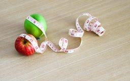 Взгляд сверху свежего красного яблока и яблока зеленого цвета с измеряя лентой Стоковое Изображение RF