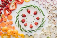 взгляд сверху свежих зрелых клубник и зеленых горохов на круглой белой плите и органических овощах стоковые изображения rf