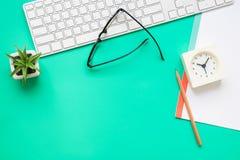 Взгляд сверху современного зеленого стола офиса с канцелярскими принадлежностями Стоковое Фото