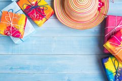 Взгляд сверху соломенной шляпы и подарочной коробки на свете - голубом деревянном flo планки Стоковое фото RF