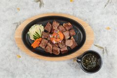 Взгляд сверху стейка Saikoro чеснока: отбензинивание wagyu кости средства редкое с семенит морковь на нагревательной плите, котор Стоковое Фото