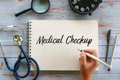 Взгляд сверху стетоскопа, лупы, часов, ручки и ручки удерживания руки писать медицинский проверку на тетради на деревянной предпо стоковая фотография