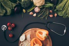 Взгляд сверху стетоскопа между зелеными овощами и деревянной доской стоковое фото