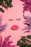 взгляд сверху стороны сделанное из губки и ложных ресниц окруженных с цветками на розовой поверхности Стоковое фото RF