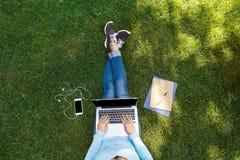 Взгляд сверху студентки сидя в парке с компьтер-книжкой Стоковое Изображение RF