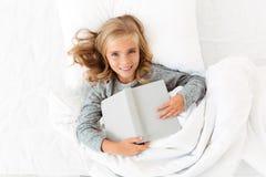 Взгляд сверху счастливой белокурой девушки лежа в кровати с серой книгой, looki Стоковая Фотография