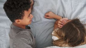Взгляд сверху счастливых multiracial пар лежа в кровати и говорить Привлекательные молодой человек и женщина в влюбленности Роман сток-видео