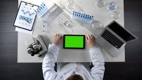 Взгляд сверху таблетки скроллинга работника лаборатории с зеленым экраном, современной лабораторией стоковые изображения