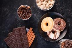Взгляд сверху таблеток шоколада, donuts, желтого сахарного песка с арахисами в шоколаде и кофейных зерен Стоковые Фото