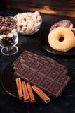 Взгляд сверху таблеток шоколада, donuts, желтого сахарного песка с арахисами в шоколаде и кофейных зерен Стоковое Фото