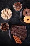 Взгляд сверху таблеток шоколада, donuts, желтого сахарного песка с арахисами в шоколаде и кофейных зерен Стоковые Изображения