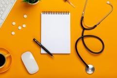 Взгляд сверху таблицы доктора с блокнотом и стетоскопом ручки, клавиатурой, рецептом и таблетками, чашкой кофе на желтом цвете стоковое фото