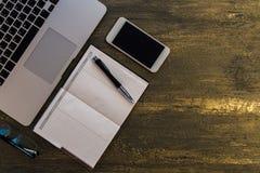 Взгляд сверху таблицы или стола с компьтер-книжкой, пустой тетрадью, ручкой и умным телефоном на старой бронзовой предпосылке Стоковое Изображение RF