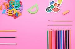 Взгляд сверху таблицы ребенка, состав номеров писем кисти красит линию ластика карандашей различную на пинке стоковое изображение rf