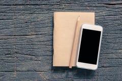 Взгляд сверху тетради мобильного телефона и коричневой бумаги с карандашем дальше Стоковые Изображения RF