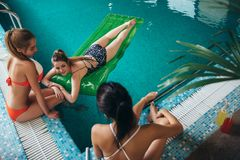 Взгляд сверху тонких молодых женских друзей ослабляя на бассейне гостиницы Стоковые Изображения RF