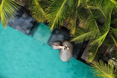 Взгляд сверху тонкой молодой женщины в бежевом бикини и соломенной шляпе ослабляя около роскошных бассейна и пальм o стоковые фото