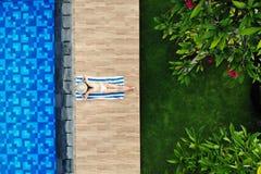 Взгляд сверху тонкой молодой женщины в белом бикини и соломенной шляпе лежа на полотенце около бассейна Задний взгляд, без сторон стоковые изображения rf