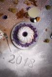 Взгляд сверху торта кольца покрытого с порошком сахара, фиолетовыми свечами, миндалиной, стеклом лимонада на светлой предпосылке Стоковое Фото