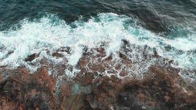 Взгляд сверху трутня бурных океанских волн ударяя и распространяя на утесах Белый и голубой брызгать волн моря сток-видео