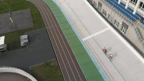Взгляд сверху трутня велодрома Киева с велосипедистами на фиксированных велосипедах шестерни Исправленные всадники шестерни трени сток-видео