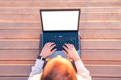 Взгляд сверху усаживания дела профессионального на деревянных шагах с руками на пустом ноутбуке экрана на заходе солнца стоковая фотография rf