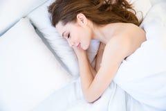 Взгляд сверху утомленной красивой молодой женщины спать на кровати стоковые фотографии rf