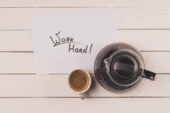Взгляд сверху чашки кофе, бумажного листа с работой надписи крепко и бака кофе Стоковые Изображения