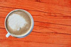 Взгляд сверху чашки кофе капучино на оранжевой деревянной деревенской таблице Стоковое фото RF