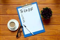 Взгляд сверху чашки кофе, eyeglasses, ручки, завода и бумаги написанных, что с СДЕЛАТЬ СПИСОК на деревянной предпосылке стоковая фотография