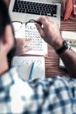 Взгляд сверху человека нося приданный квадратную форму дозор рубашки и руки изучая иероглифы стоковое фото