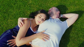 Взгляд сверху: Человек с беременной женой лежит на зеленой траве видеоматериал