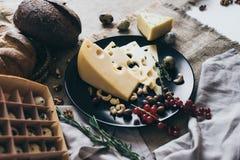 Взгляд сверху черного блюда и коробки яичка Очень вкусные закуски на этом блюде: дорогой сыр с травами, ягодами и гайками Стоковое фото RF