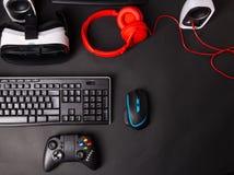 Взгляд сверху шестерня игры, мышь, клавиатура, кнюппель, шлемофон, шлемофон VR на черной предпосылке таблицы стоковое фото
