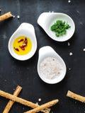 Взгляд сверху 3 шлюпок соуса с розовым солью, маслом со специями и листьями свежей петрушки стоковые фото