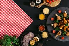 взгляд сверху checkered салфетки, овощей, соусов и очень вкусных зажаренных в духовке картошек с цыпленком на черноте Стоковые Изображения RF