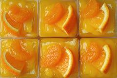 Взгляд сверху Rowed вверх по тортам апельсина мандарина покрытым с свежими апельсинами в стеклянных шарах Стоковое фото RF
