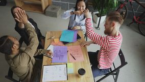 Взгляд сверху start-up команды дела мульти-этнических сотрудников давая максимум 5 все вместе сидя на таблице в офисе сток-видео